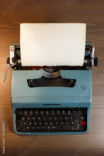 Foto op Plexiglas Retro Vintage typewriter header with blank paper on wooden background, top view.