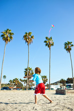 Boy Flying A Kite  At The Beach.