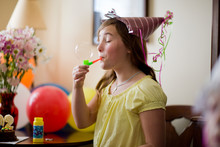 Girl In Party Hat Blowing Bubbles