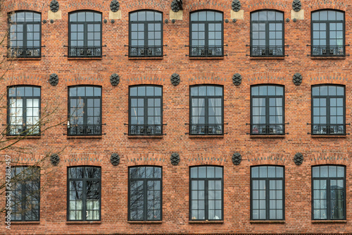 Żyrardów, Poland. Window with iron frame and red bricks wall of old factory.