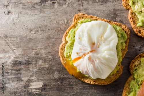 Close up avocado toast with poached egg on wooden table. Top view. Copyspace