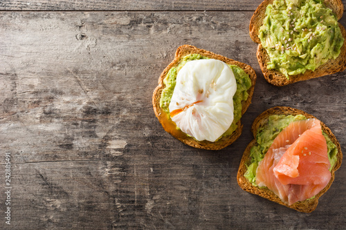 Toasted breads with avocado, poached eggs and salmon. Top view. Copyspace