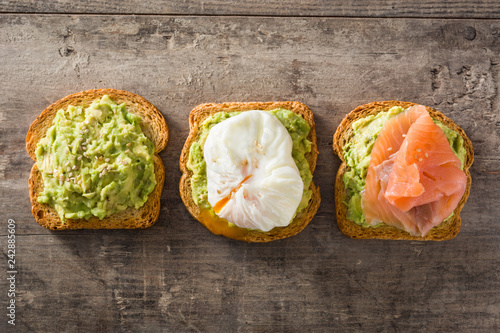 Toasted breads with avocado, poached eggs and salmon. Top view.