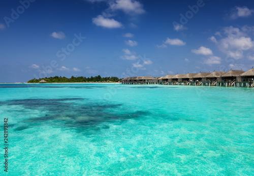 Obraz premium Widok laguny na Malediwach z turkusem, tropikalną wodą i głębokim błękitnym niebem