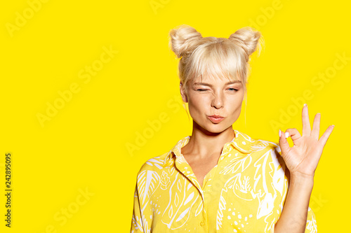 Portrait of young woman showing ok sign and winking. Cheerful blonde model with two buns posing in studio. Copy space in left side. Summer and positivity concept. Isolated on yellow background