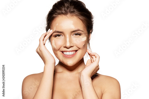 Foto Portrait of happy laughing girl making natural make-up using tonal foundations different shades