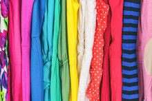 Closet Women's Fashion Outfits Clothes Arranged In Rainbow Colors Assorted. Clothing Store Dresses Hanging On Shopping Rack. Variety Of Fabrics And Patterns, Wool, Polyester, Polka Dots, Stripes.