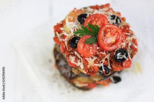 melanzane gratinate al parmigiano, pomodorini e olive su tavolo di legno bianco