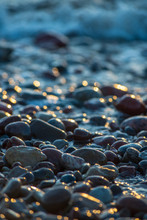 Abstract Details Of Rocky Beach Pebbles In Sunset By The Sea