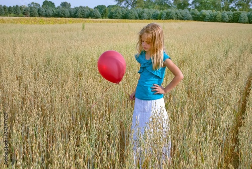 Photo  young Caucasian girl in Michigan wheat field with red balloon