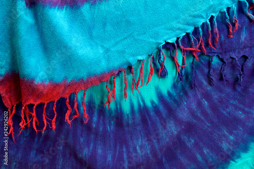 Deurstickers Kristallen Two different tie dyed background cloths folded and layered showing multicolored tassels.