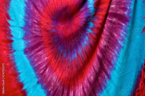 Fotografie, Obraz  Close up of vibrant multi colored batik tie dyed fabric background showing spira