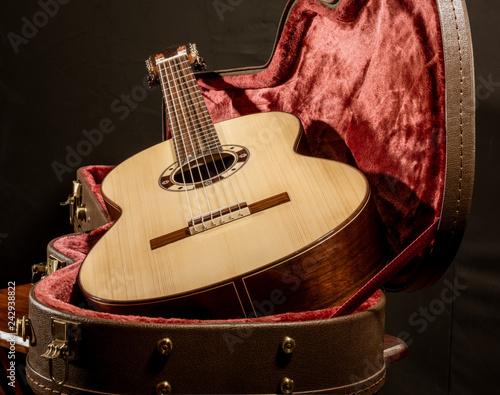 Fotografie, Obraz  Acoutic guitar sits in red velvet lined case