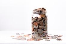 Money Spilling Over Jar On A White Background