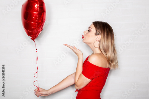 Photo  Beautiful girl with red balloon on hand sending kiss