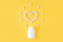 Pills In Shape Of Heart Dropped From Bottle On Yellow Background. Flat Lay, Top View.