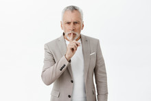 Old Man Teaching Son How Raise Money. Portrait Of Wise Senior Male Entrepreneur In Elegant Suit Showing Shush Gesture With Serious And Calm Expression Telling Secrets Of Success Over Gray Background