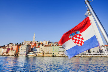 Flag of Croatia with Rovinj town at background, Istria, Croatia. Travel tourism concept. Croatian vacations