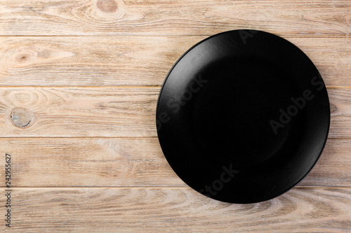 Poster de jardin Vache Directy above Empty black matte dish for dinner on orange wooden background with copy space