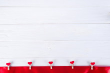 Clothespins With Red Hearts On A Red Ribbon As A Border On A White Wooden Background With Space For Text. The Concept Of Valentine Day, Copy Space