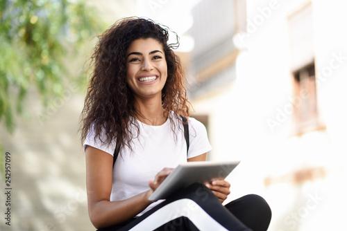 fototapeta na drzwi i meble Smiling African woman using digital tablet outdoors