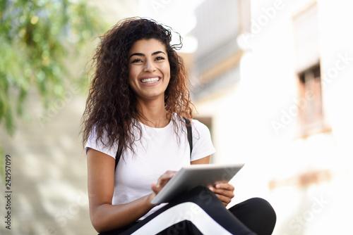 fototapeta na szkło Smiling African woman using digital tablet outdoors