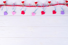 Clothespins With Red Hearts On A Ribbon As A Border On A White Wooden Background With Space For Text. The Concept Of Valentine Day, Copy Space