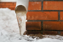 Drain Pipe With Frozen Stream Of Water Near House Brick Wall