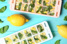 Flat Lay Composition With Ice Cube Tray, Mint And Lemons On Wooden Background