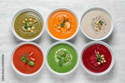 Various soups in bowls on wooden background, top view. Healthy food