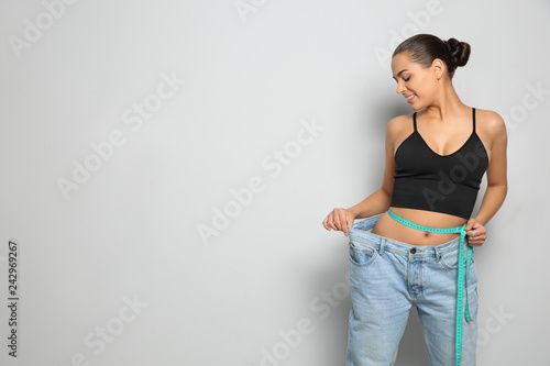 Slim woman in oversized jeans with measuring tape on light background, space for text. Weight loss