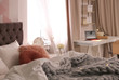 Large comfortable bed and workplace with laptop in stylish apartment. Room interior