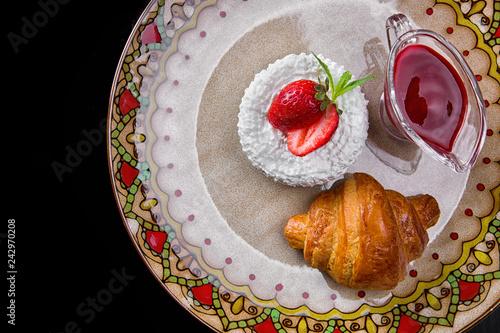 Plakat Śniadanie. Croissant z serem, truskawki i dżem, na kolorowym talerzu, na czarnym tle. Widok z góry