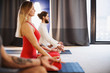 Healthy beautiful young people woman and two men are meditating sitting in the lotus position on floor mats in a cozy little room with large windows. Healthy lifestyle and strong body concept