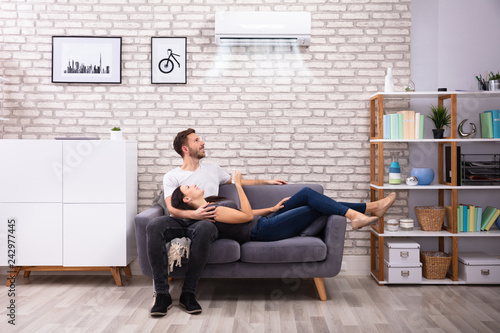 Photo Happy Couple Operating Air Conditioner At Home
