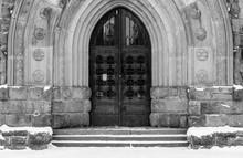Gothic Oak Door Entrance On Public Institution In Transylvania, Romania In Black And White.