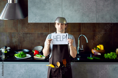 Foto Funny loser man male guy with metal sieve, frying pan, wooden kitchen utensils and apron trying to cook, failed and need help on grey modern loft kitchen