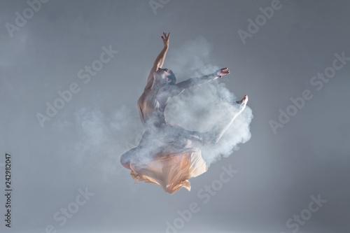 Fototapeta Elegant woman female girl ballerina dancer in beige dress dancing, making performance and dance element in fog dust smoke fume on isolated grey background scene. Dancing in cloud concept obraz