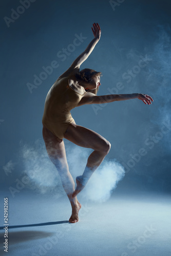 Dancing in cloud concept. Muscle brunette beauty female girl adult woman dancer athlete in fog smoke fume wearing dance bodysuit making emotional dance element performance on isolated grey background Wall mural