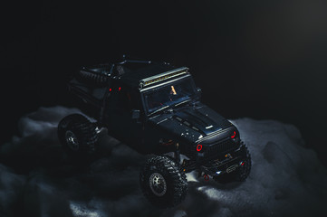 Radio-controlled car in the snow at night, lights shine. Christmas entertainment gift rc car
