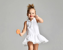 Young Pretty Toddler Girl Kid With Big  Sweet Lollypop Candy In White Dress On Grey