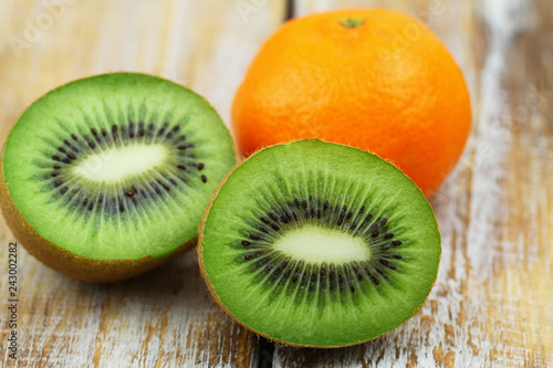 Closeup of two halves of fresh kiwi fruit and orange on rustic wooden surface