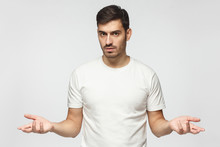 Young Man Spreading Hands Not Knowing What To Do, Isolated On Gray Background