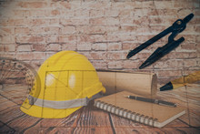 Yellow Construction Helmet And Work Tool On Wood And Old Brick Wall.
