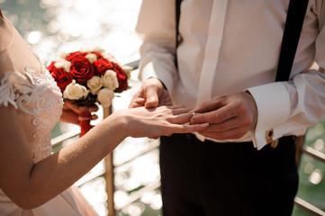 Obraz na płótnie Canvas Broom putting on a golden wedding ring to a tender bride finger