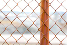 A Closeup Of A Section Of A Rusty Chain Link Fence. One Fence Post Is Visible. Industrial Site In Background Outside Depth Of Field.