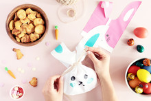 Happy Easter! Woman Make Easter Basket With Traditional Decorations And Sweets Near Cute Gift Bunny Bags On Pink Table, Top View And Flat Lay