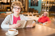 Content attractive senior lady in glasses sitting at wooden table and holding book while looking at camera in modern restaurant
