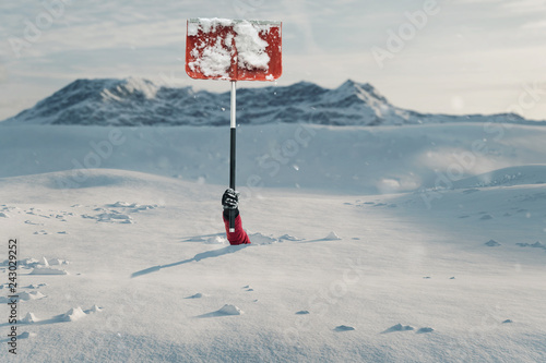 Photographie Hand mit roter Schneeschaufel grabt sich aus und macht auf sich aufmerksam