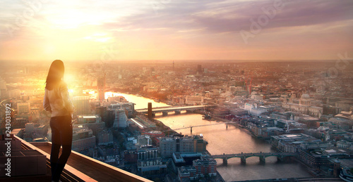 Foto auf Leinwand Beige Young woman looking at the City of London at sunset. Planning the future, life and joy concept.